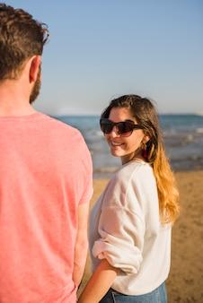 Mujer joven sonriente que se coloca con sus gafas de sol que llevan del novio que miran sobre hombro en la playa