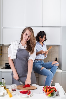Mujer joven sonriente que corta el paprika con el cuchillo y su amigo que usa el teléfono móvil en el fondo