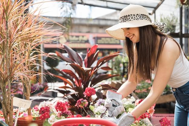 Mujer joven sonriente que corta la planta floreciente