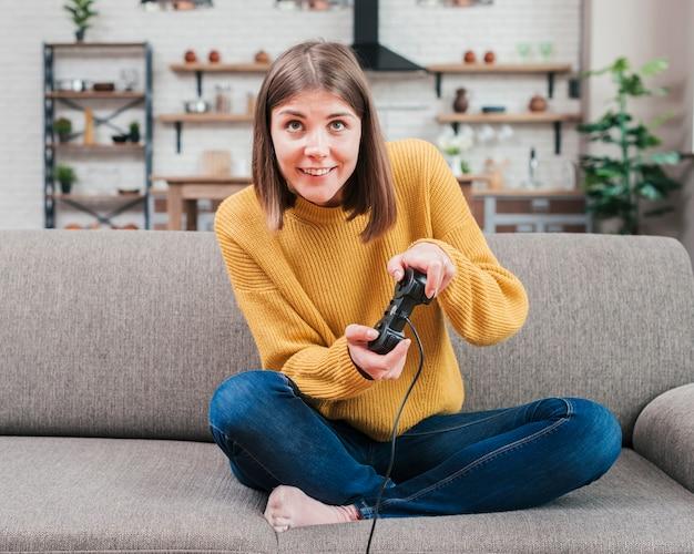 Mujer joven sonriente que se divierte jugando el juego video de la consola en casa
