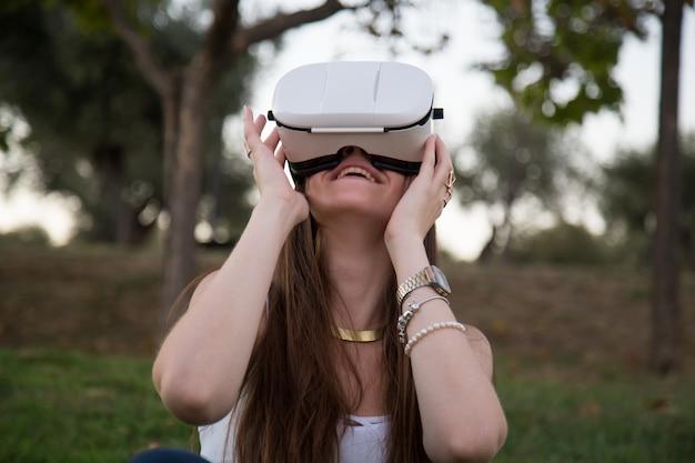 Mujer joven sonriente que se divierte mientras que usa los vidrios de realidad virtual en parque.