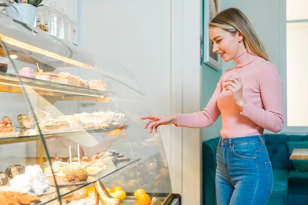 Mujer joven sonriente que elige la torta que se coloca delante del gabinete de cristal