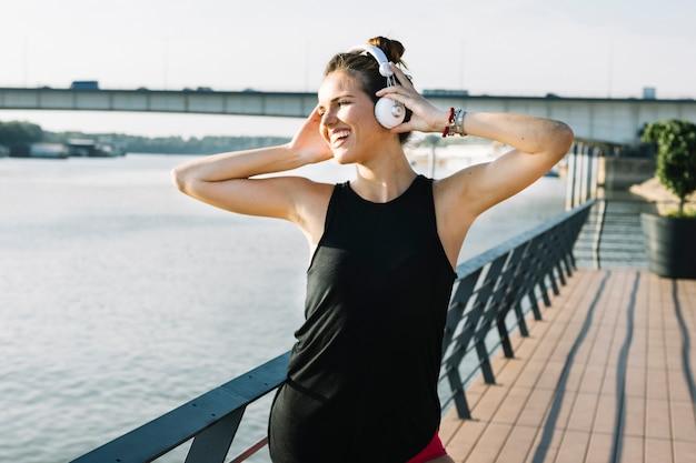 Mujer joven sonriente que escucha la música en el auricular cerca del río
