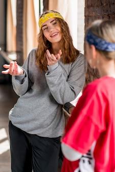 Mujer joven sonriente que habla con su amigo