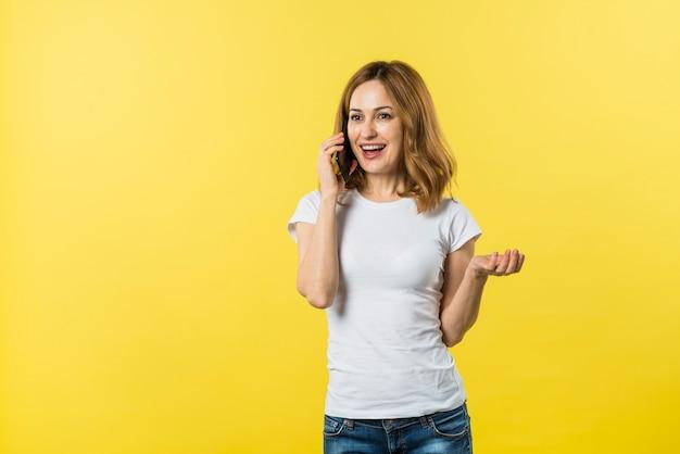 Mujer joven sonriente que habla en el teléfono móvil contra el contexto amarillo