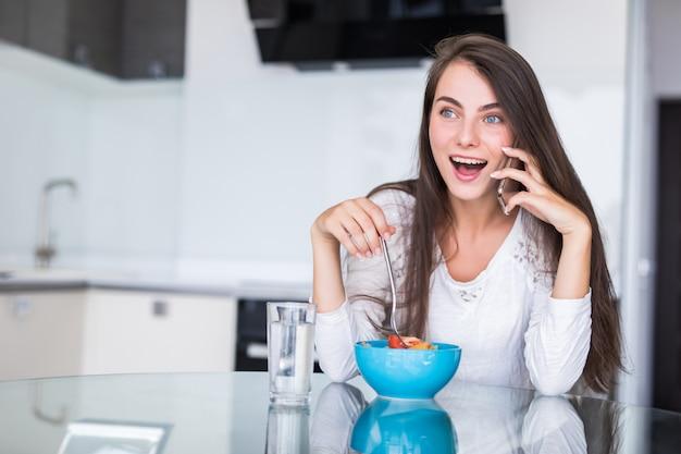 Mujer joven sonriente que habla en el teléfono móvil mientras que come la ensalada en una cocina