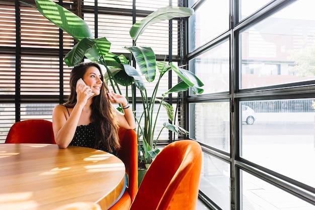 Mujer joven sonriente que habla en el teléfono móvil en el restaurante