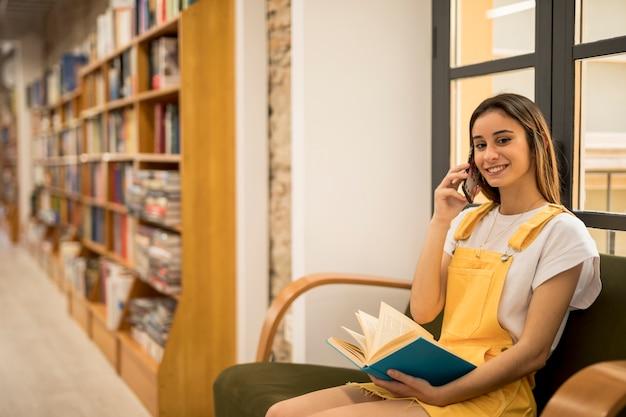 Mujer joven sonriente que habla en el teléfono y que sostiene el libro azul