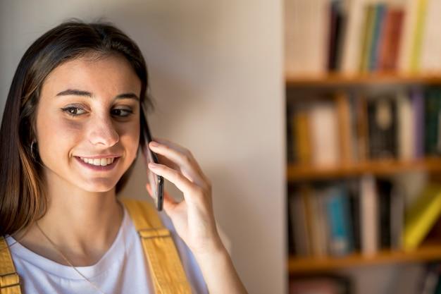 Mujer joven sonriente que habla en la ventana que hace una pausa del teléfono