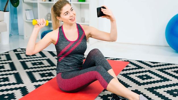 Mujer joven sonriente que hace ejercicio con la pesa de gimnasia amarilla que toma el selfie en el teléfono móvil