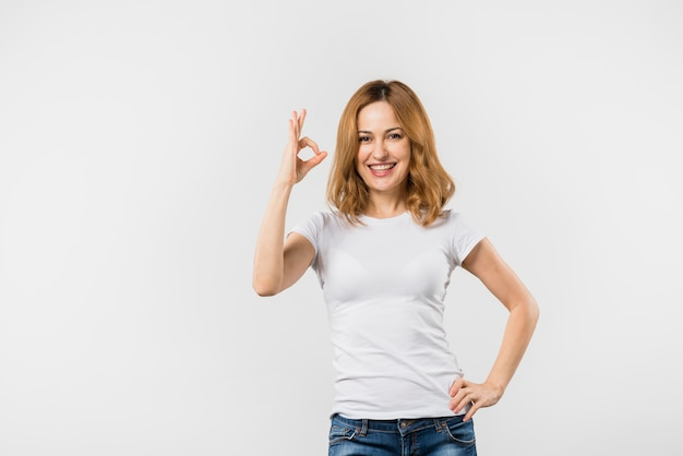 Mujer joven sonriente que hace gesto aceptable contra el contexto blanco