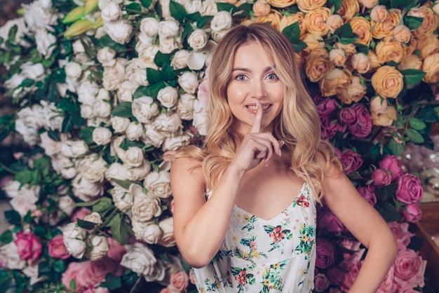 Mujer joven sonriente que hace el gesto reservado que se coloca delante del contexto de las rosas