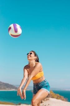 Mujer joven sonriente que juega a voleibol en la playa