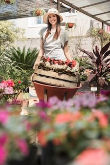 Mujer joven sonriente que lleva el cajón de flores en carretilla