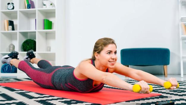 Mujer joven sonriente que miente en la estera roja del ejercicio que ejercita con pesas de gimnasia amarillas