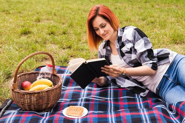 Mujer joven sonriente que miente en el libro de lectura de la manta en la comida campestre