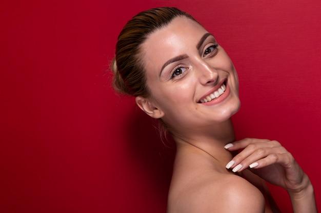 Mujer joven sonriente que mira la cámara