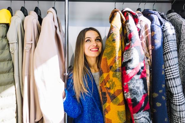 Mujer joven sonriente que mira las capas que cuelgan en un estante