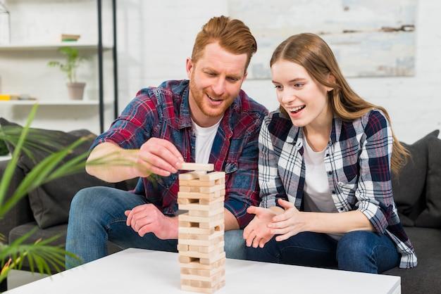 Mujer joven sonriente que mira a su novio que arregla los bloques de madera en casa