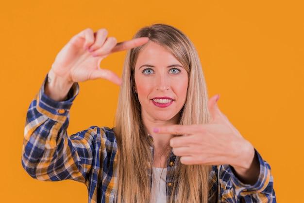 Mujer joven sonriente que mira a través de marco de la mano contra un contexto anaranjado