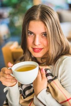 Mujer joven sonriente que muestra infusión de hierbas en la taza blanca