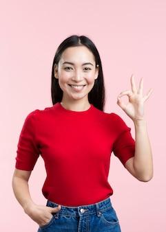 Mujer joven sonriente que muestra la muestra aceptable