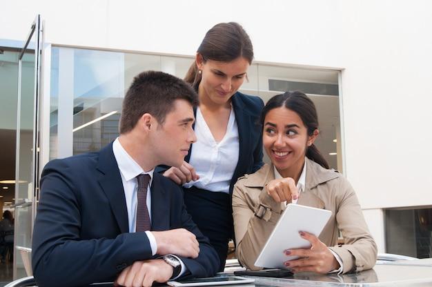 Mujer joven sonriente que muestra la pantalla de la tableta a los hombres de negocios