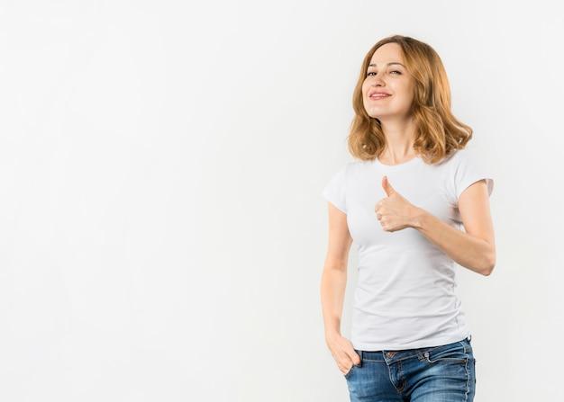 Mujer joven sonriente que muestra el pulgar encima del gesto contra el fondo blanco