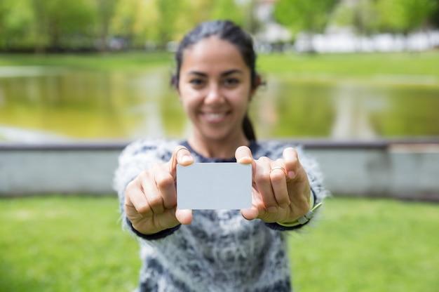 Mujer joven sonriente que muestra la tarjeta plástica en blanco en parque de la ciudad
