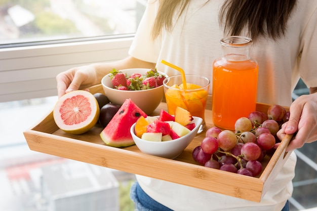Mujer joven sonriente que se opone a la ventana que sostiene la bandeja de frutas y de jugo
