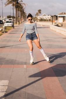 Mujer joven sonriente que patina en la acera en ciudad