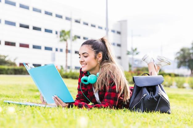 Mujer joven sonriente que pone en el césped que lee el libro en el campus universitario