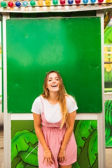 Mujer joven sonriente que presenta delante de la pared verde en el parque de atracciones