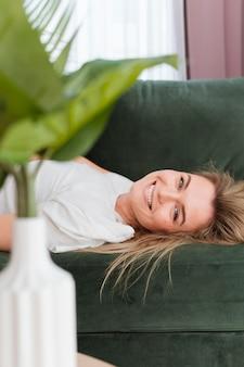 Mujer joven sonriente que se relaja en casa y planta