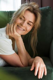 Mujer joven sonriente que se relaja en casa