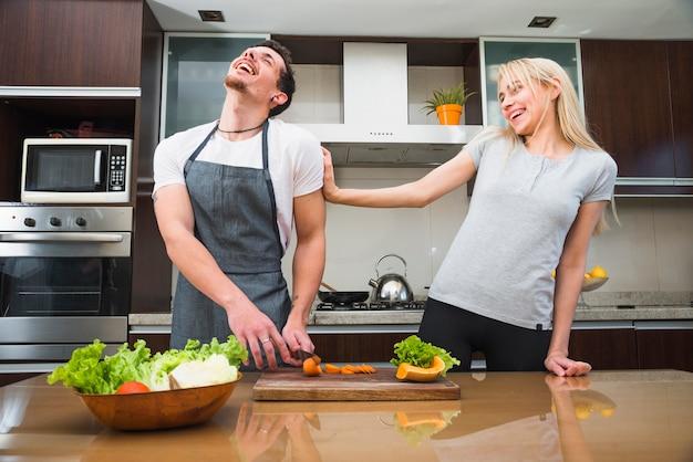 Mujer joven sonriente que se ríe con su zanahoria del corte del marido en la tajadera de madera