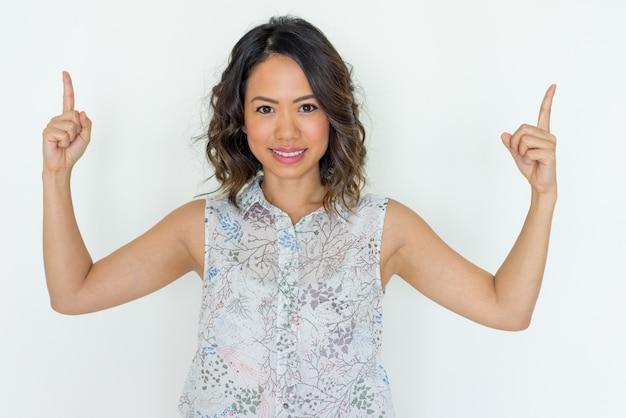 Mujer joven sonriente que señala hacia arriba con ambos índices