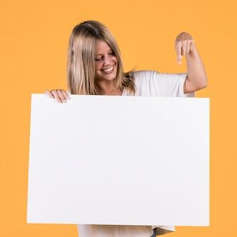 Mujer joven sonriente que señala el dedo índice en el cartel en blanco blanco