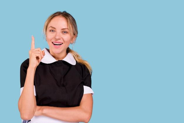 Mujer joven sonriente que señala el dedo índice en dirección ascendente y que mira la cámara