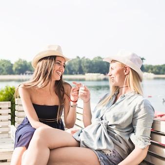 Mujer joven sonriente que se sienta en el banco que señala el dedo el uno al otro