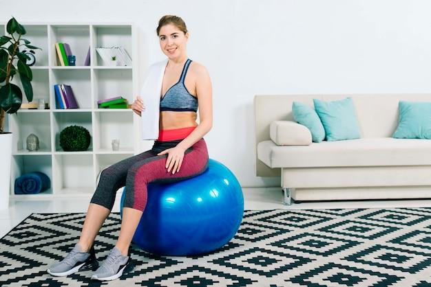 Mujer joven sonriente que se sienta en la bola azul de los pilates que sostiene la toalla sobre hombro