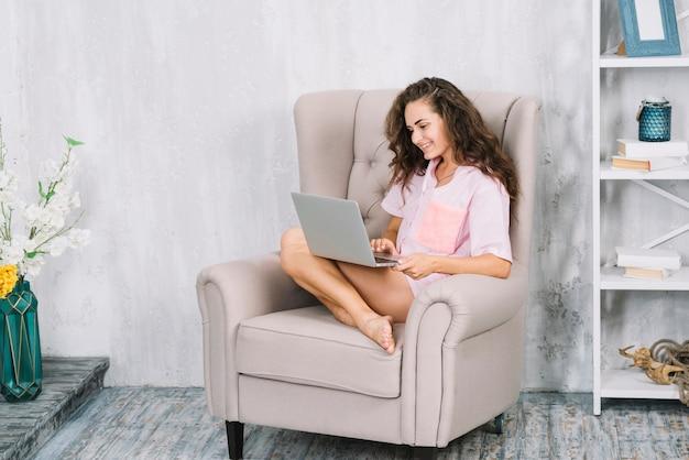 Mujer joven sonriente que se sienta en la butaca usando el ordenador portátil