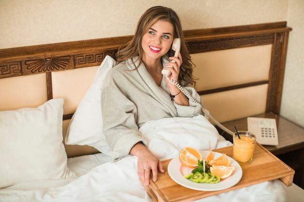 Mujer joven sonriente que se sienta en cama con el desayuno sano que habla en el teléfono