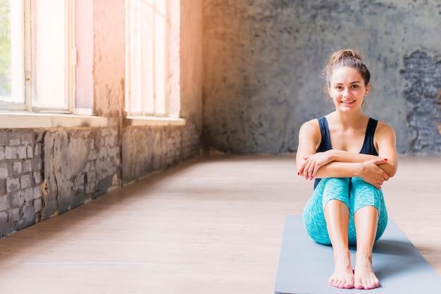 Mujer joven sonriente que se sienta en la estera de la yoga que mira la cámara