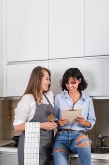 Mujer joven sonriente que se sienta en el fregadero de cocina que muestra receta a su amigo
