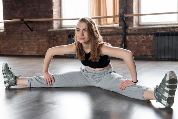 Mujer joven sonriente que se sienta en el piso que estira su pierna aparte
