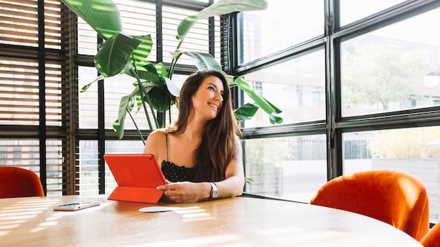 Mujer joven sonriente que se sienta en el restaurante con la tableta digital