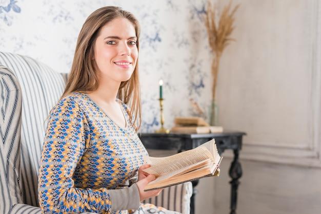 Mujer joven sonriente que se sienta en la silla que sostiene el libro en manos