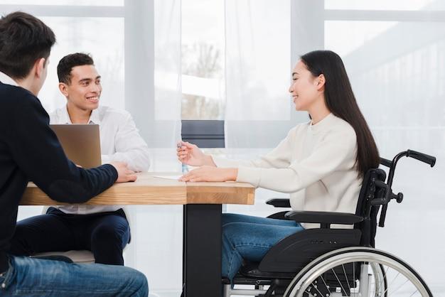 Mujer joven sonriente que se sienta en la silla de ruedas que tiene reunión de negocios corporativa con sus dos colega