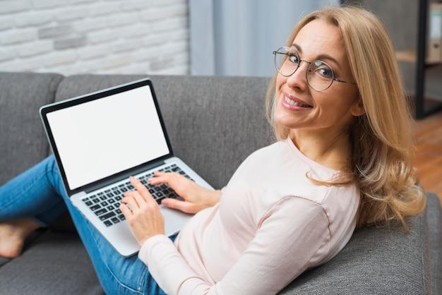 Mujer joven sonriente que se sienta en el sofá con el ordenador portátil en su revestimiento que mira la cámara